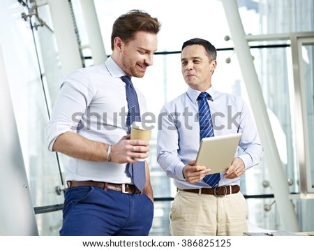 two caucasian corporate people discussing business using tablet computer in office. - stock photo