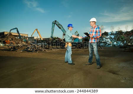 two caucasian engineers standing in recycling center outdoors shaking hands - stock photo