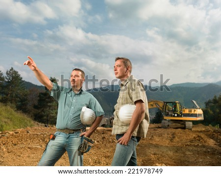 two caucasian engineers standing, one of them pointingat construction in progress - stock photo