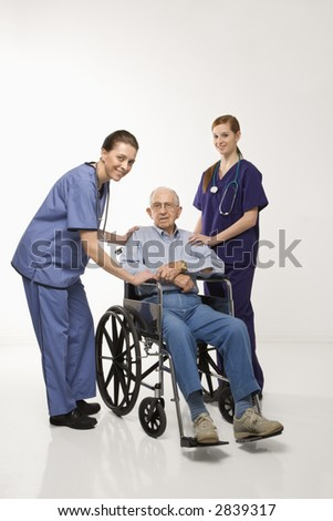 Two Caucasian females wearing scrubs with elderly Caucasian male in wheelchair. - stock photo