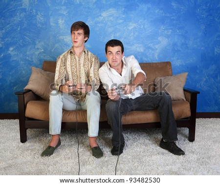Two Caucasian friends with controller play video game - stock photo