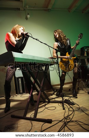 Two caucasian girls singing into microphone and playing the guitar. - stock photo