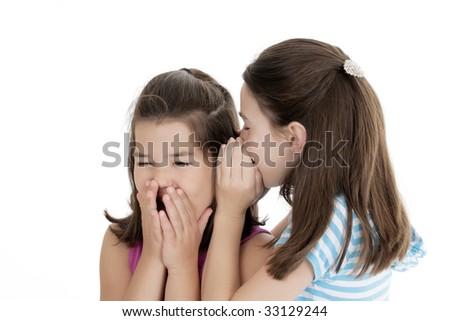 Two Caucasian girls telling secrets on white background - stock photo