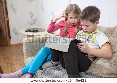Two Caucasian kids having fun with pad while sitting on sofa in domestic room - stock photo
