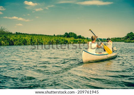 Two caucasian males paddling in a canoe