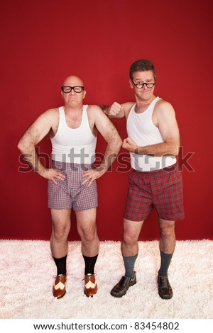Two Caucasian men wearing boxer shorts show off biceps over maroon background - stock photo