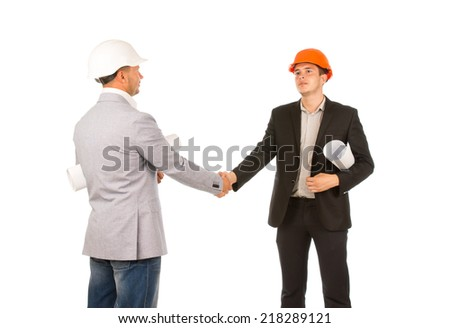 Two Caucasian Middle Age Engineers Shaking Hands with Blueprints. Isolated on White Background. - stock photo