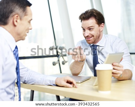 two caucasian office people discussing business using tablet computer in office. - stock photo