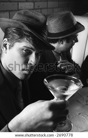 Two Caucasian prime adult males in retro suits sitting at table with cocktails. - stock photo