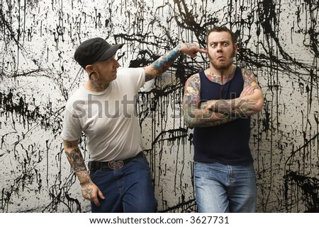 Two Caucasian tattooed men standing against paint splattered background. - stock photo