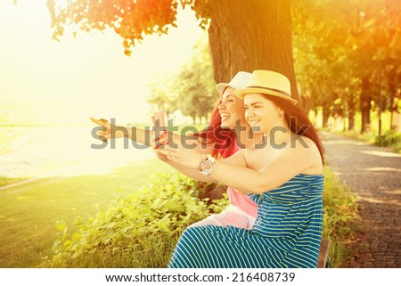 Two Caucasian teenage girls in park taking a photo with smartphone. Redhead and brunette young women photographing something outdoors in autumn. - stock photo