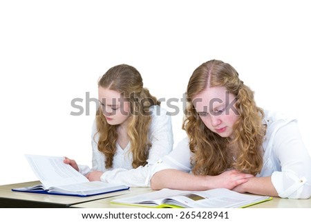 Two caucasian teenage girls studying books for education. The european sisters with long hair sit side by side reading textbooks. Isolated on white background with space for adding text. - stock photo