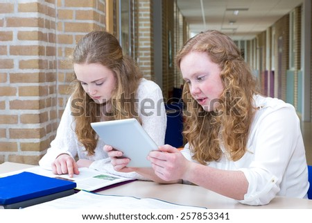 Two caucasian teenage girls studying with tablet and books in long school corridor - stock photo