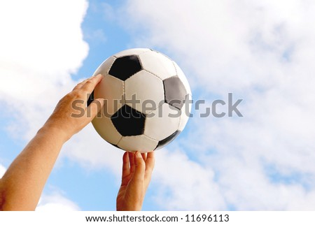 Two caucasian white hands catching a traditional black and white football in front of blue sky background with clouds