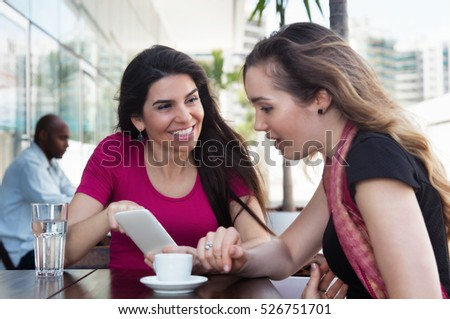 Two caucasian woman looking at phone in a restaurant