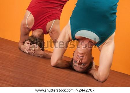 Two Caucasian women perform Sirasana headstand positions - stock photo