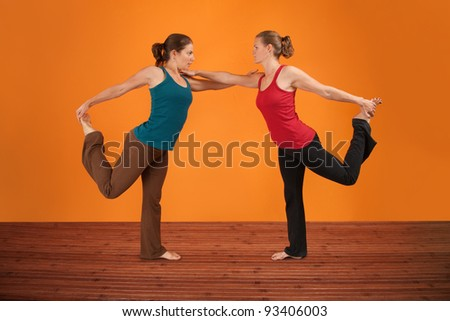 Two Caucasian women perform yogasana over orange background