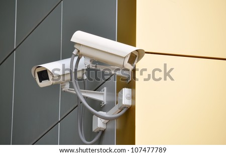 Two CCTV cameras on the cone of the morden building - stock photo