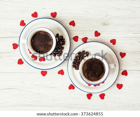 Two ceramic cups of coffee with red hearts on the wooden background. Valentine's Day. Symbol of love. - stock photo