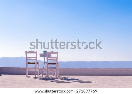 Two chairs and a small table at the top of the roof of one of the houses on Santorini, Greece. Shot of a sunny, clear day - stock photo