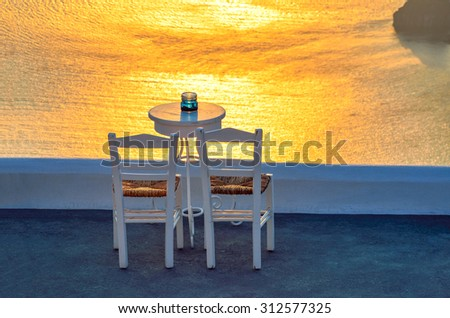 Two chairs and a small table with a wonderful view in Santorini, Greece. - stock photo