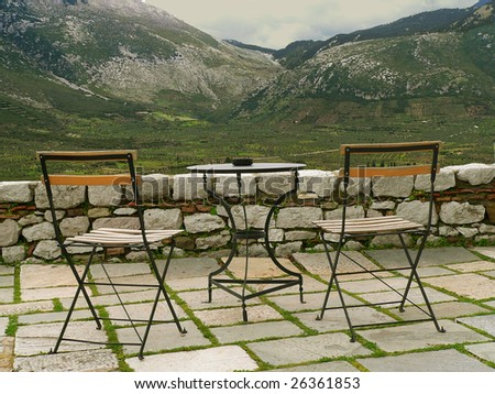 two chairs and a table on a stone terrace facing an open valley