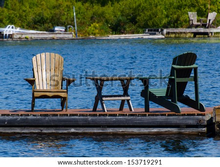 Two chairs and a table on the dock - stock photo