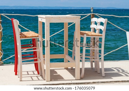 Two chairs and table from restaurant on the beach and horizon over sea in the background - stock photo