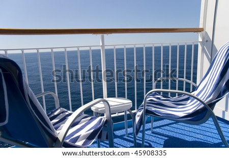 Two chairs and towels on a cruise ship's balcony. - stock photo