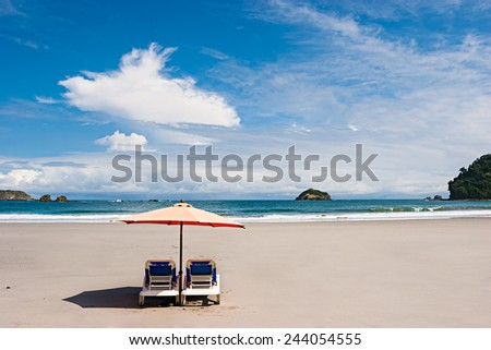 Two chairs and umbrella at the beach. Manuel Antonio, Costa Rica. - stock photo