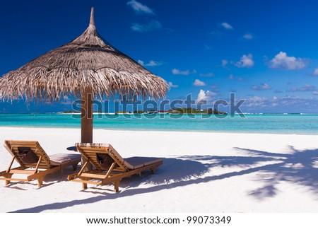 Two chairs and umbrella on a beach with shadow from palm tree - stock photo