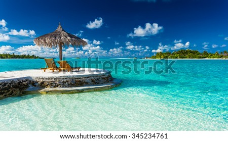 Two chairs and umbrella on a jetty on a tropical island, Maldives - stock photo