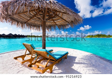 Two chairs and umbrella on stunning tropical beach - stock photo