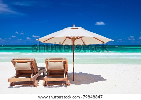 Two chairs and umbrella on stunning tropical beach in Tulum, Mexico - stock photo