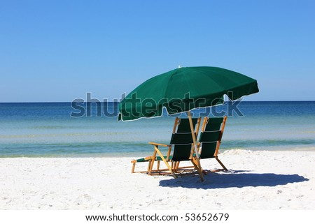 two chairs and umbrella on white sand beach - stock photo