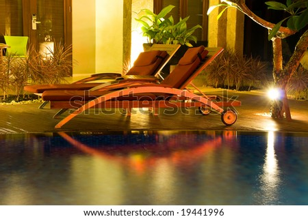 Two chairs by the swimming pool in the night - stock photo