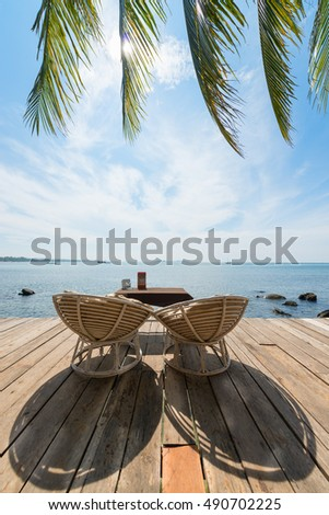 Two chairs on a beautiful wooden deck with a table ashtray and menu facing the sea and palm leaves in Sihanoukville, Cambodia.