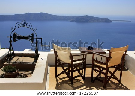 Two chairs on a hill overlooking the sea; relaxing scene; - stock photo