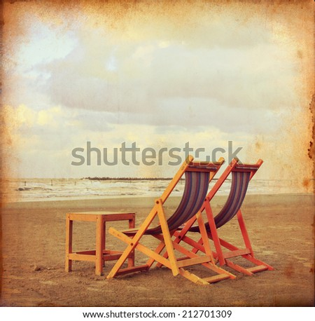 Two chairs on beach with small table