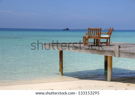 Two chairs on jetty on Maldive Islands