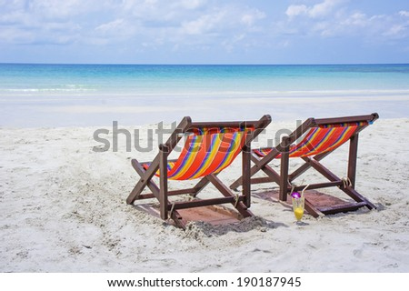 Two chairs on the white sand before blue sea on beautiful tropical beach
