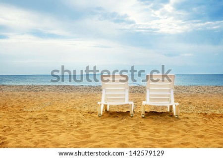 Two chairs on tropical beach - stock photo