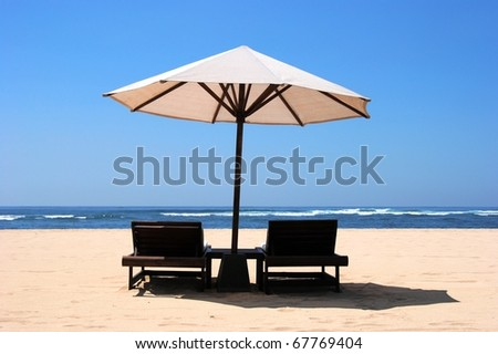 Two chaise lounges under an umbrella on sandy - stock photo