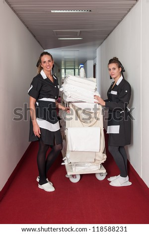 Two chambermaid women cleaning in a hotel.