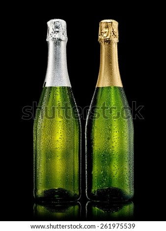 Two champagne bottles with drops on black background - stock photo