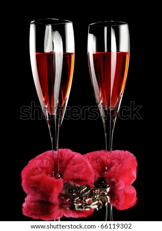 Two champagne flutes cuffed with red furry handcuffs romantic concept isolated on black background - stock photo