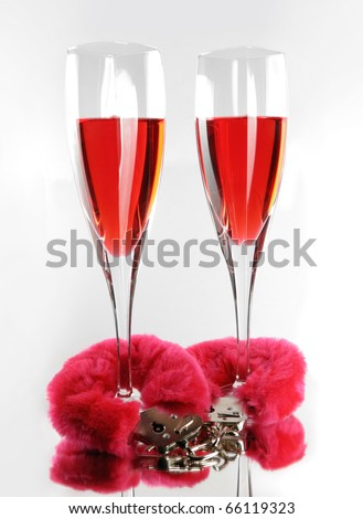 Two champagne flutes cuffed with red furry handcuffs romantic concept isolated on white background - stock photo