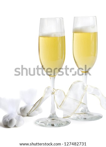 Two champagne flutes with champagne and ribbons with hard candies - stock photo