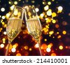 two champagne flutes with golden bubbles make cheers on colorful light bokeh background with space for text - stock photo