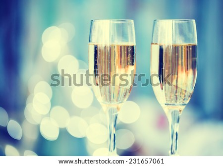 Two champagne glass on christmas bokeh background. Blue toned - stock photo